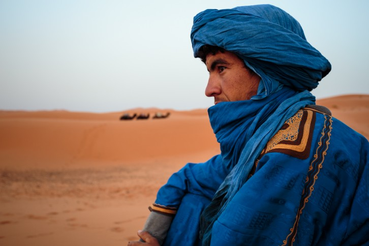 Our Berber guide stares at some very small camels, in the Sahara desert